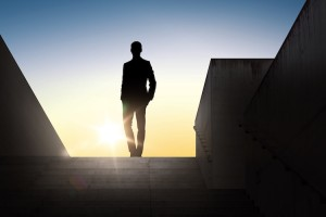 business and people concept - silhouette of businessman standing on stairs over sun light background