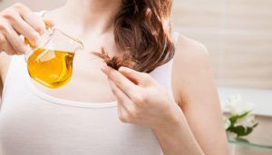 woman-applying-oil-mask-to-hair-tips-768x437