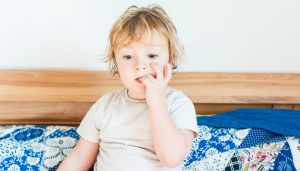 Interior portrait of a cute toddler boy biting nails